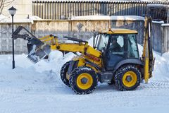 Yellow tractor clears snow stock image