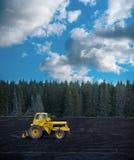 Yellow tractor on dark field Stock Photography