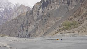 A yellow tractor digging sand in Hunza river royalty free stock images