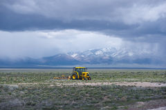Yellow Tractor with plow working on field with grass. Yellow tractor with a plow working in the field in the middle of Nevada, cultivating land for growing food royalty free stock images