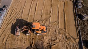Yellow tractor repairs the road aerial view royalty free stock image