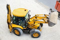 Yellow tractor leads road works royalty free stock photos