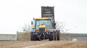 Yellow tractor spreading fertilizer Royalty Free Stock Photo