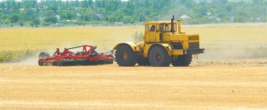 Yellow tractor at sunset works on field disco after harvesting Stock Image