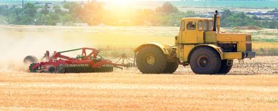Yellow tractor at sunset works on field disco after harvesting Royalty Free Stock Image