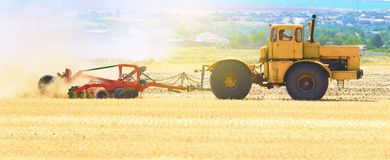 Yellow tractor at sunset works on field disco after harvesting Royalty Free Stock Photos