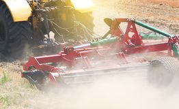 Yellow tractor at sunset works on field disco after harvesting Royalty Free Stock Photography
