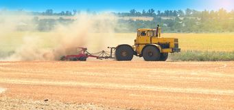 Yellow tractor at sunset works on field disco after harvesting Stock Photos