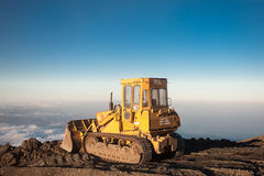 Yellow tractor at the top of the Etna mountain with view on the. Blue sky with Yellow tractor at the top of the Etna mountain with view on the clouds and the Stock Photo