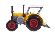 Yellow tractor toy on white background Royalty Free Stock Photo