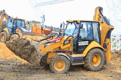 The yellow tractor in work earthwork. VOLGOGRAD, RUSSIA - April 23, 2018: The yellow tractor in work earthwork with sand, at construction of the Arena stadium Stock Photo
