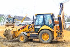 The yellow tractor in work earthwork. VOLGOGRAD, RUSSIA - April 23, 2018: The yellow tractor in work earthwork with sand, at construction of the Arena stadium Stock Photography