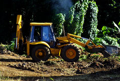 Yellow tractor at work. Tractor tilling the soil in a village in Mauritius Stock Photo