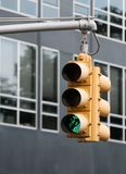 Yellow Traffic light with green sigh flashing Royalty Free Stock Photo
