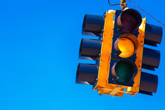 A yellow traffic light with a sky blue background Stock Images