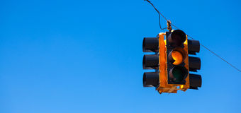 A yellow traffic light with a sky blue background Royalty Free Stock Photography