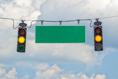 Yellow Traffic Lights With Blank Street Sign. Horizontal shot of two yellow traffic lights hanging from a cable with a blank street sign in-between with blue sky Stock Photos