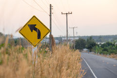 Yellow traffic sign and grass flower beside road Stock Photo