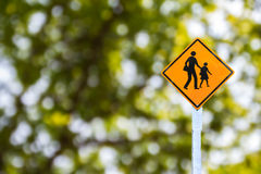 Yellow traffic sign on green blurred bokeh Royalty Free Stock Photography