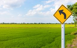 Yellow traffic sign on road with green nature rice field backgro stock images