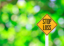 Yellow traffic sign text for stop loss green bokeh abstract ligh Stock Photos