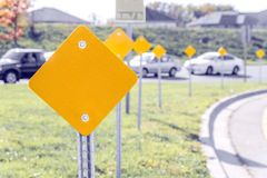 Yellow traffic signs along the turn of a highway on ramp. With cars in the background stock image