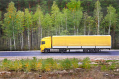 Yellow trailer goes on highway Stock Photo