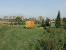 Yellow trailer on a green farm royalty free stock image