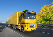 Yellow trailer with a load on the track Royalty Free Stock Photo