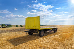 Yellow trailer in a stubble field Stock Image