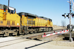 Yellow Train. A yellow train rolling through a railroad crossing Stock Photo
