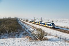 Yellow train in Dutch rural winter landscape Stock Photography