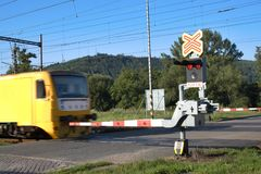 Yellow train goes over the railway crossing Stock Images