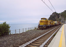 Yellow train parked in front of the ocean in Corniglia, Italy. Royalty Free Stock Image