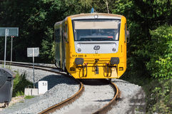 A yellow train proceeding on the tracks. Beside a dense growth of greenery and a milestone that reads 5.3 Royalty Free Stock Photos
