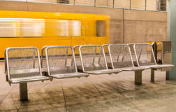 Yellow Train speeding behind metal Seats. In a generic subway station Royalty Free Stock Photography