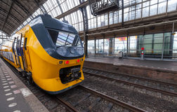 Yellow train stands in Amsterdam station Stock Images