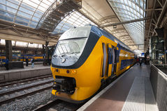 Yellow train stands on the central railroad station in Amsterdam Royalty Free Stock Photos