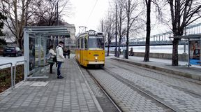 Yellow tram arriving at a stop with passengers stock image