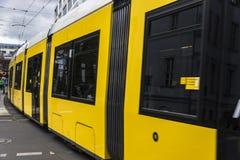 Yellow tram circulating in Berlin, Germany. Yellow tram circulating while passengers waiting on a platform in Berlin, Germany Stock Photos