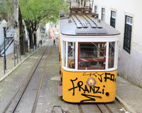 Yellow tram with graffity in Lisbon Stock Photo