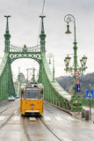 Yellow tram on the Liberty Bridge in Budapest, Hungary. Royalty Free Stock Photos