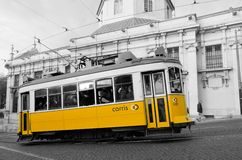 Yellow tram in Lisbon. Famous yellow tram of line 28 in the old town on Lisbon going up of hill. Inside the tram a courious man is looking at camera royalty free stock image