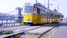 Yellow tram passes by in slow motion. Chain Bridge in background stock footage