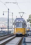 Yellow tram ride along the rails Royalty Free Stock Photos