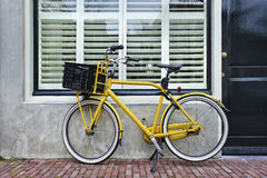 Yellow transport bike parked against renovated house, Amsterdam, Netherlands. Yellow retro transport bike parked against a renovated house, Amsterdam, The Royalty Free Stock Photos