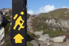 Yellow trekking sign on a wooden pole Royalty Free Stock Image