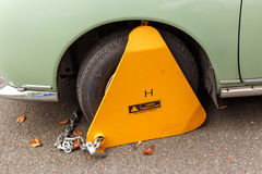 Yellow triangle car wheel parking clamp attached. Stock Photography