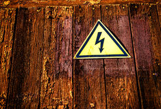 Yellow Triangle Electricity Warning Sign. Yellow shaped electricity warning sign with a black electric bolt on a dark aged wood grunge style background Stock Image