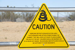 A yellow triangle sign with Snake caution warning. At a rest top in the desert along a California Highway Royalty Free Stock Image